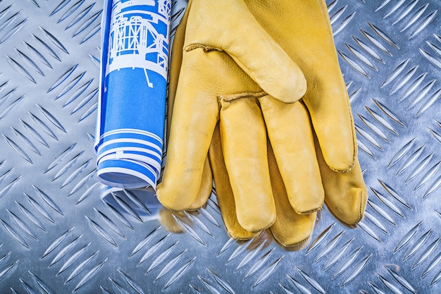 Blue blueprints and leather safety gloves on fluted metal surface