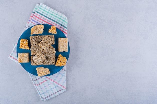Bordo blu di caramelle con vari dadi e semi su pietra.