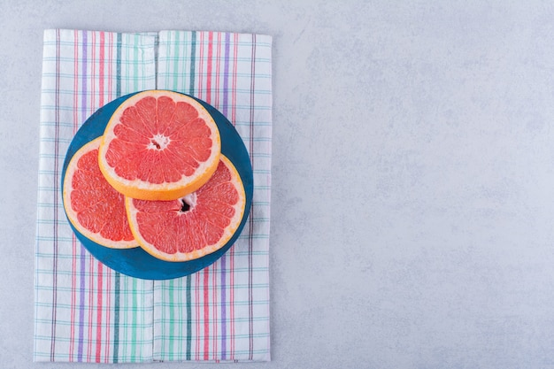 Blue board of fresh grapefruit slices on stone table.