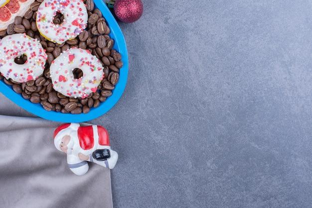 Un bordo blu pieno di chicchi di caffè e ciambelle