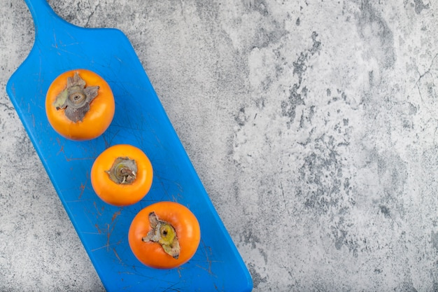 Blue board full of ripe persimmon fruits on stone.