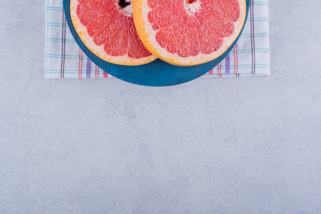 石のテーブルに新鮮なグレープフルーツのスライスの青いボード。