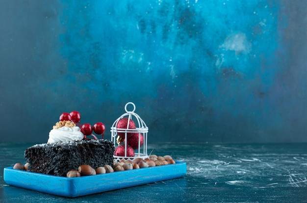 A blue board with a piece of chocolate cake and macadamia nuts. high quality photo