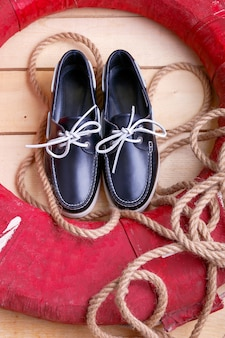 Blue boat shoes on wooden background near red lifebuoy and rope. top view.