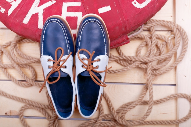 Blue boat shoes on wooden near lifebuoy and rope. top view.