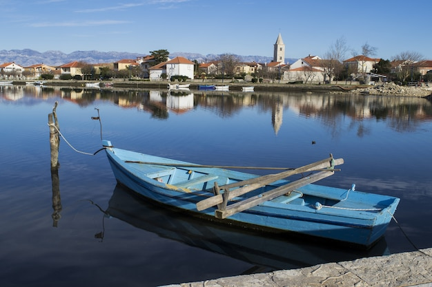 Синяя лодка пришвартована у пристани в деревне