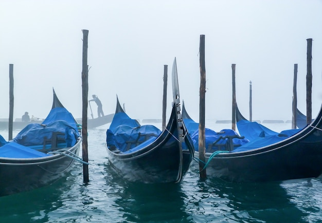 Blue boats parked and a foggy white sky