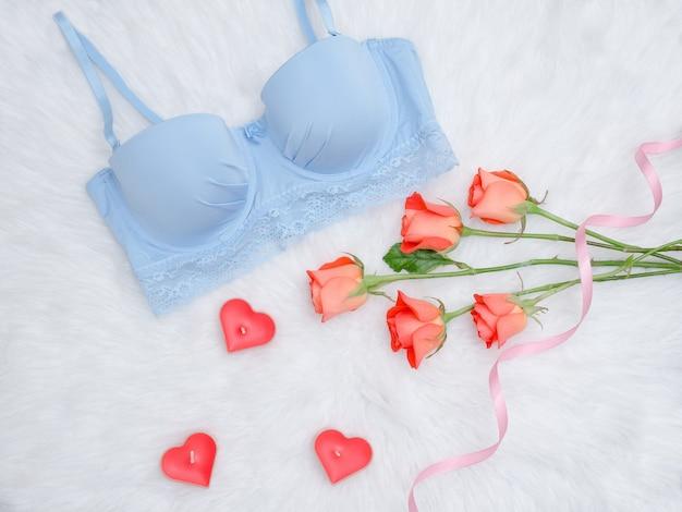 Синий лиф и оранжевые розы с кружевом на белом меху. модная концепция. вид сверху