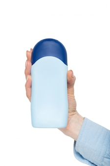 Blue bottle for cosmetic product in a female hand.