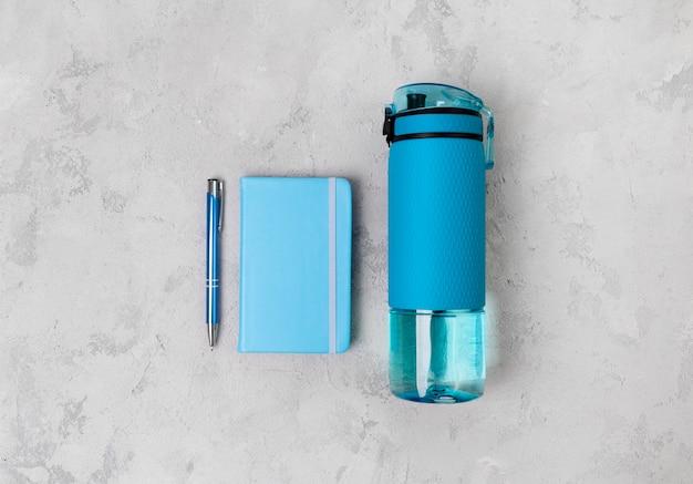 Синяя бутылка воды и блокнот. спортивный инвентарь на сером бетонном столе