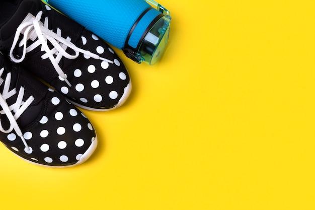 水と靴の青いボトル。創造的なテーブルの上のスポーツ用品。