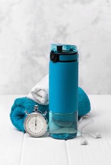 Синяя бутылка воды, полотенца, наушники и секундомер. спортивный инвентарь на белом деревянном столе