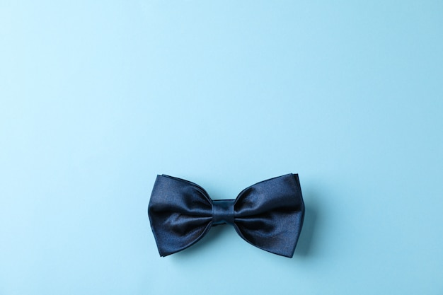 Blue bow tie on color background, space for text