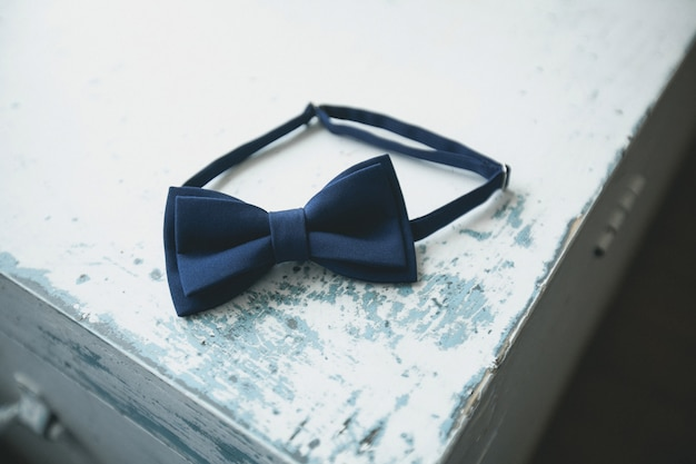Blue bow tie, a fashion accessory for a man, groom or businessman, on an old shabby, peeling wooden table, close-up. preparing the groom for the wedding day