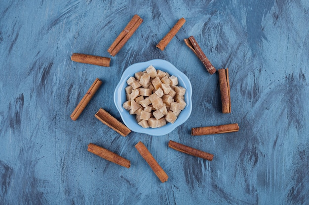 Blue bowl of brown sugar cubes and cinnamon sticks on blue surface.