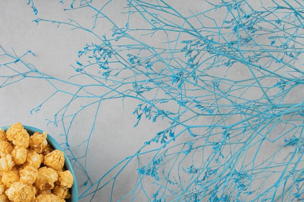 Blue bowl of caramel flavored popcorn next to decorative branches on marble background.