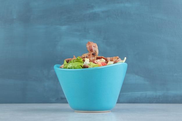 Una ciotola blu di carne di pollo su uno sfondo di marmo.