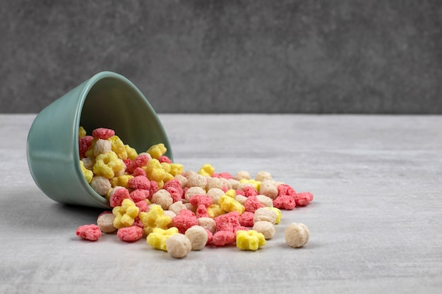 Blue bowl of colorful corn flakes on stone.