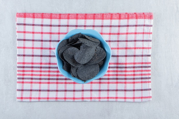 Blue bowl of crispy black chips and tablecloth on stone.