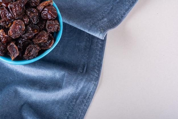 Ciotola blu di prugne organiche secche poste su sfondo bianco. foto di alta qualità