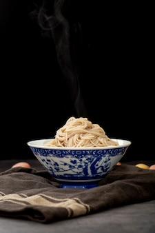 Blue bowl filled with noodle on a grey cloth