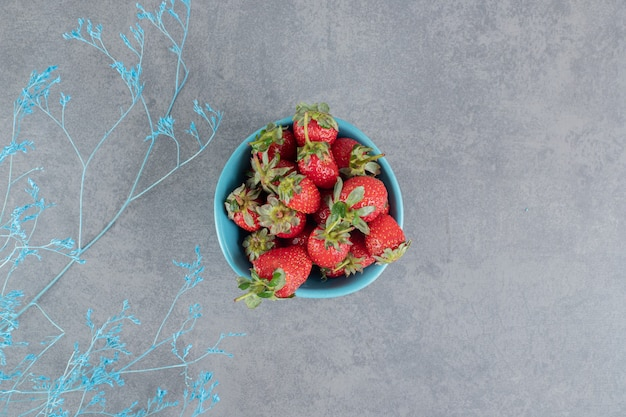 A blue bowl full of delicious strawberries . high quality photo
