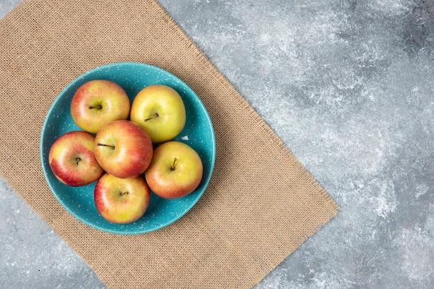 Синяя миска, полная свежих яблок на мраморе.
