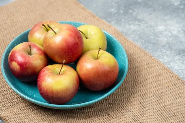大理石の新鮮なリンゴでいっぱいの青いボウル。
