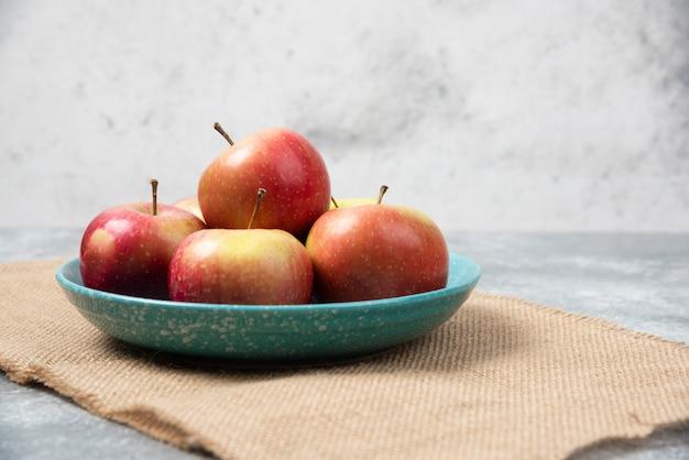 대리석에 신선한 사과 가득한 파란색 그릇입니다.