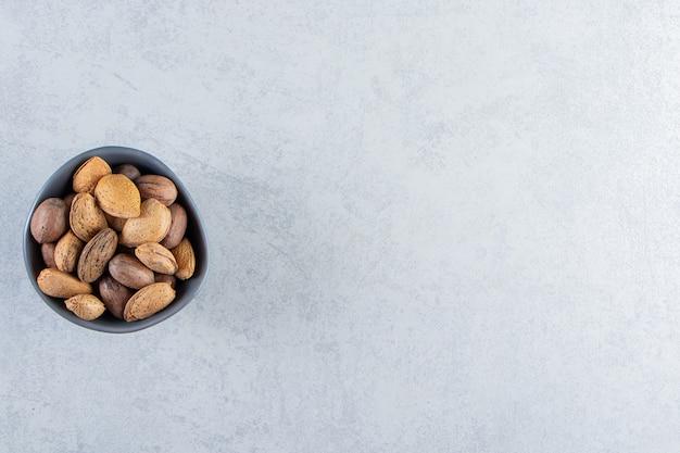 Голубая миска, полная очищенного миндаля и грецких орехов на каменном фоне.