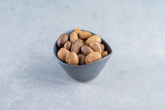돌 배경에 껍질을 벗긴 아몬드와 호두로 가득 찬 파란색 그릇.