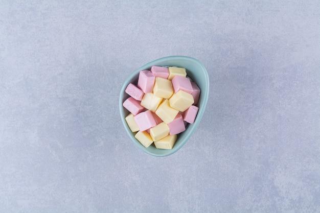 Una ciotola blu piena di dolci rosa e gialli pastila