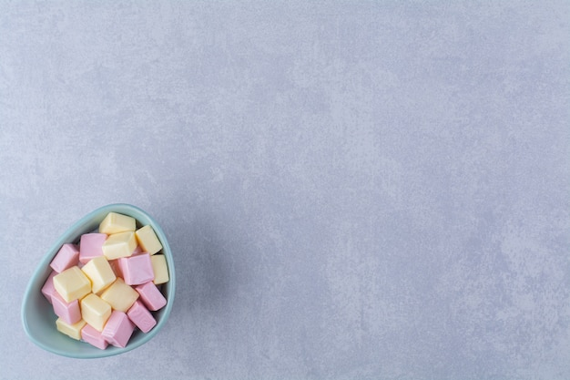 A blue bowl full of pink and yellow sweet confectionery pastila