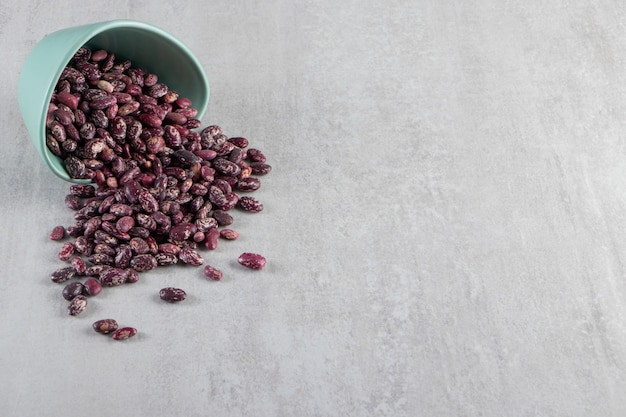 Blue bowl full of raw beans on stone background.