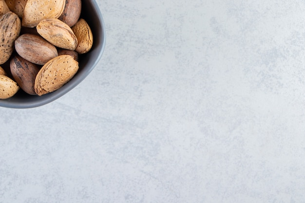 Blue bowl full of shelled almonds and walnuts on stone background.