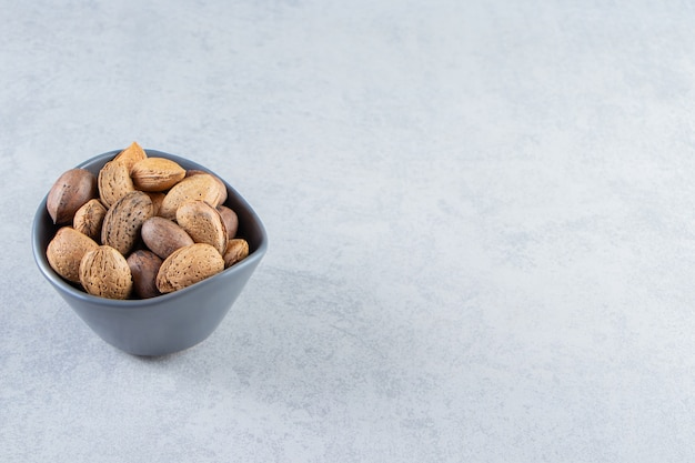 Ciotola blu piena di mandorle sgusciate e noci su pietra.