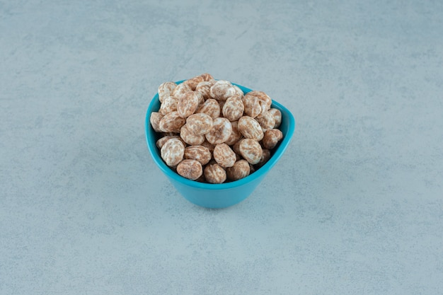 Una ciotola blu piena di pan di zenzero dolce e delizioso sulla superficie bianca white