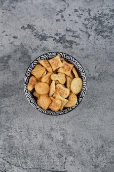 Ciotola blu piena di vari cracker salati su marmo.
