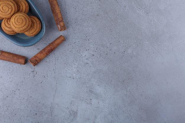 Ciotola blu di mini torte alla cannella con bastoncini di cannella su pietra.