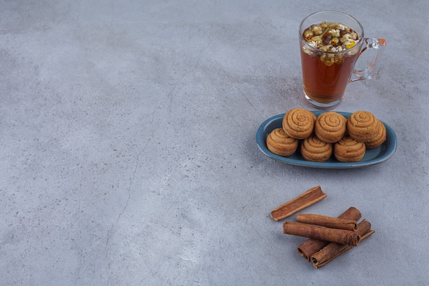 Blue bowl of mini cinnamon cakes with glass of tea on stone background.