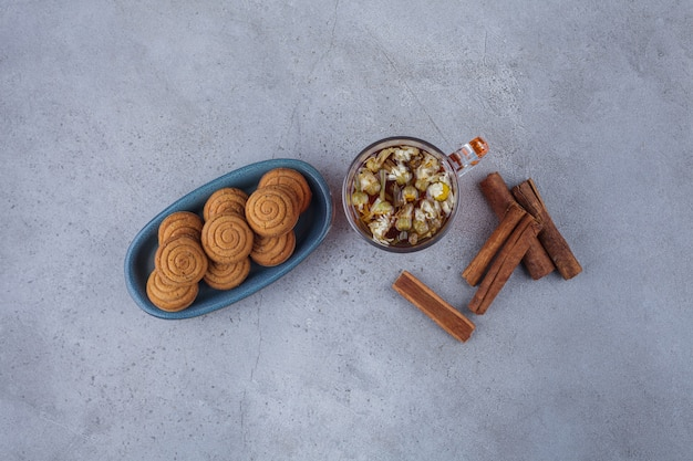 Blue bowl of mini cinnamon cakes with glass of tea on stone surface.