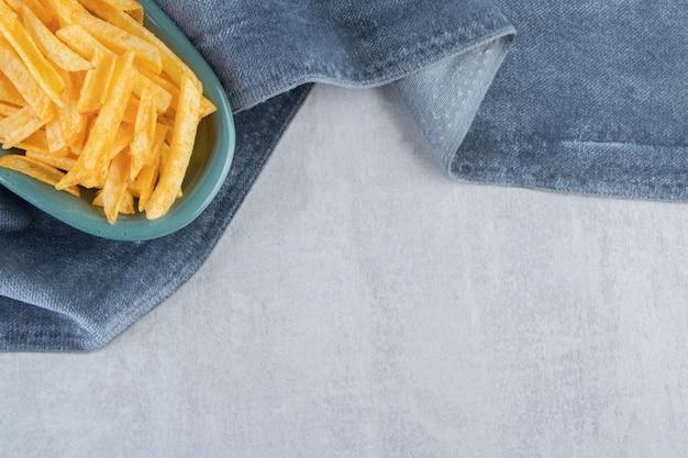 파란색 천에 파삭 파삭 한 감자 스틱의 파란색 그릇.