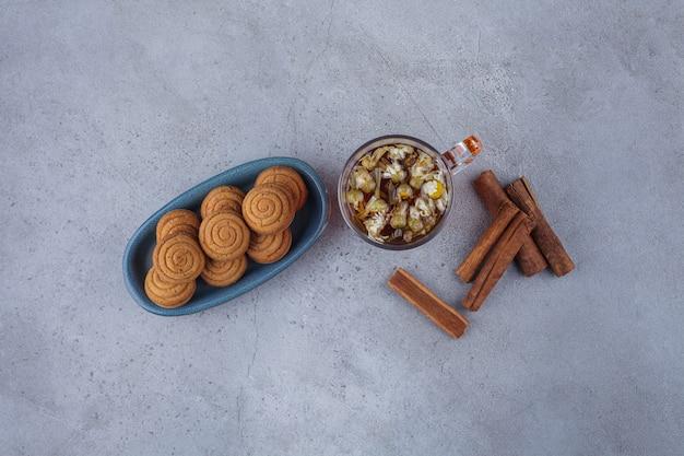Синяя миска мини-пирожных с корицей со стаканом чая на каменной поверхности.