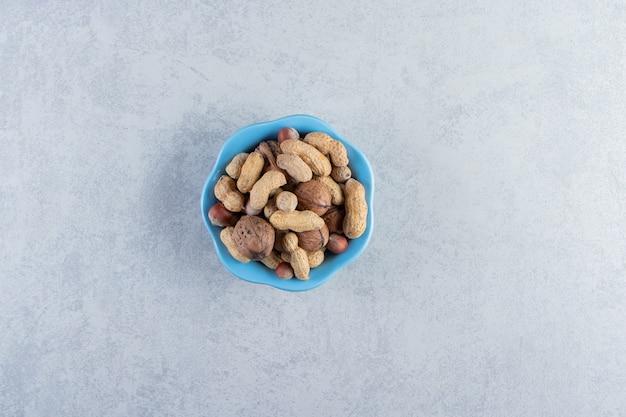 Голубая чаша органических орехов на каменном фоне.