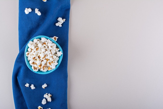 Синяя миска соленого попкорна для ночи кино на белом фоне. фото высокого качества