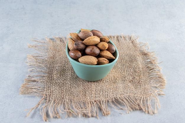 Голубая миска очищенного миндаля и грецких орехов на каменном фоне.