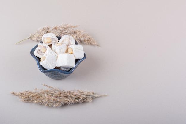 흰색 바탕에 견과류와 함께 달콤한 디저트의 파란색 그릇. 고품질 사진