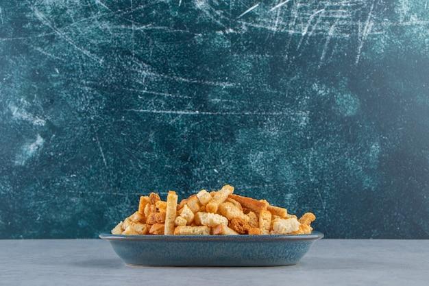 돌 배경에 맛있는 바삭한 크래커의 파란색 그릇.