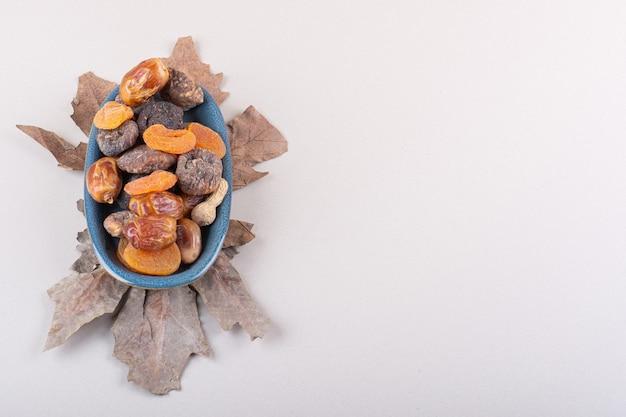 흰색 바탕에 다양 한 유기농 견과류와 과일의 파란색 그릇. 고품질 사진