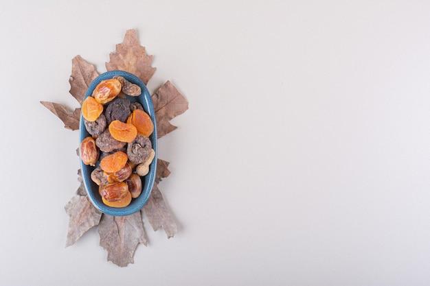 다양한 유기농 견과류와 과일의 파란색 그릇